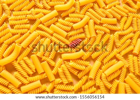 One pink pasta among others. Difference and uniqueness concept