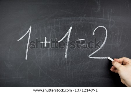 One plus one equals two written on chalkboard #1371214991