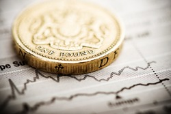One pound coin on fluctuating graph. Rate of the pound sterling (shallow DOF)