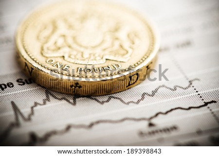 One pound coin on fluctuating graph Rate of the pound sterling shallow DOF