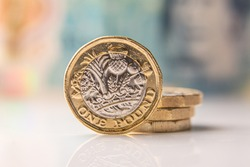 one pound coin with a 10 pound bill in the background