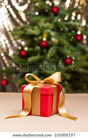 One present with gold ribbon, in front of a Christmas tree