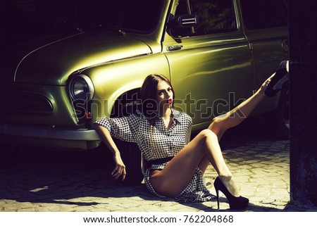 One pretty sensual thinking straight slim fashionable young woman with long legs in black high heeled shoes sitting on road near beautiful retro car golden color outdoor sunny day, horizontal picture #762204868