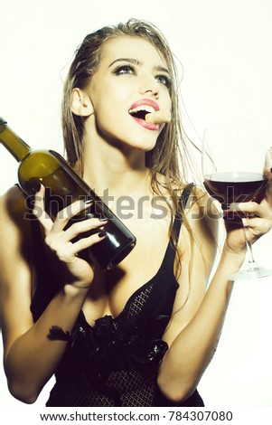 One pretty young sexy woman in black underwear with long wet hair holding wine bottle glass and cork in mouth standing in studio on white background, vertical picture #784307080