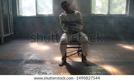 One psycho man sitting being tied to a chair in mental hose Stock photo ©