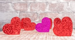 One purple heart among many red hearts. Valentine's day concept.