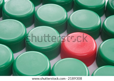 One red and many green plastic caps