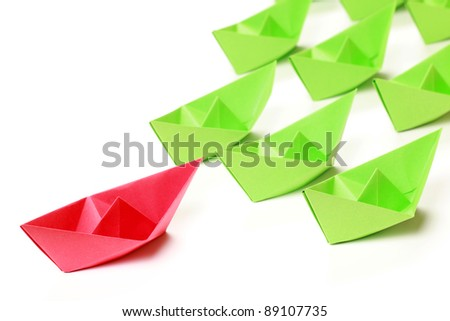 One red and several green paper boats on white background