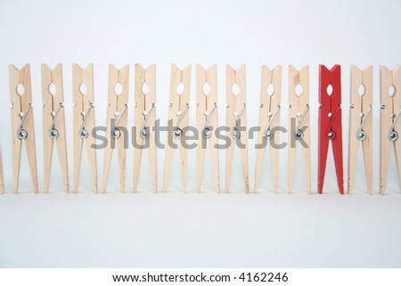 one red clothespin in a line of regular ones