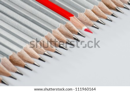 One red color pencils among lead pencils