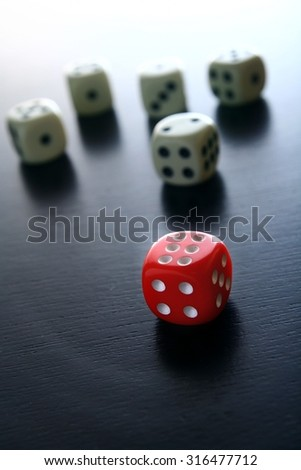 One Red game dice in front of five white game dice