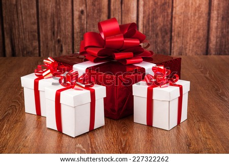 one red gift box white gift boxes on a wood background