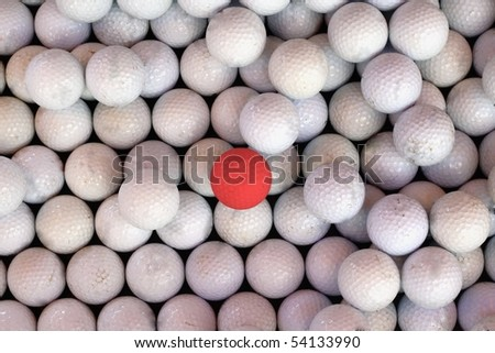 One Red Golf Ball Amongst a Sea of White Golf Balls.