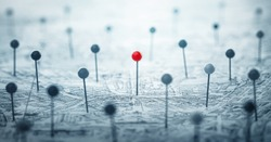 One red pin on the city map among many other colorless pins. Concept on the topic of personality, leadership, choice, travel, navigation,  geography etc.. Shallow depth of focus. Pins on map.