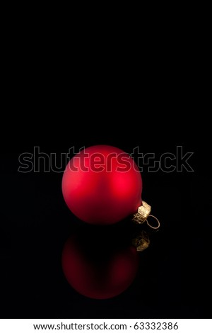 One red satin Christmas ball on black background with reflection