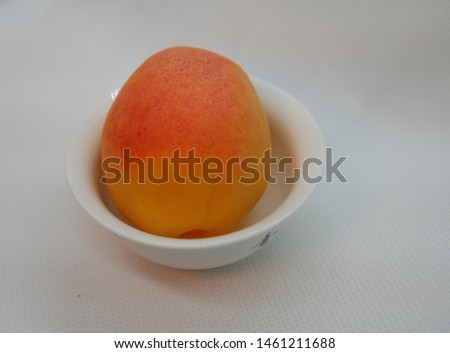 one ripe apricot in a small white porcelain plate on a white background. Natural vitamin. Healthy food. vegetarian food.