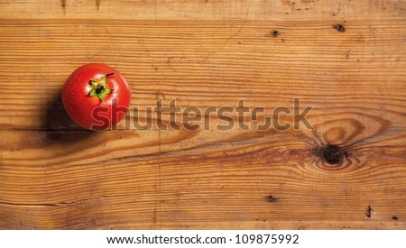 One ripe tomato on a decorative board.