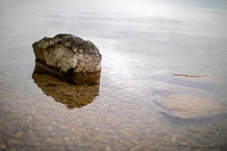 one rock washed by water on the shallow bank