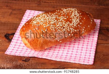 One roll bread on napkin on wooden table