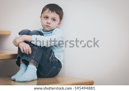 one sad little boy sitting on the stairs in house at the day time. Concept of sorrow.