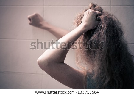 one sad woman sitting on the floor near a wall and holding her head in her hands - stock photo