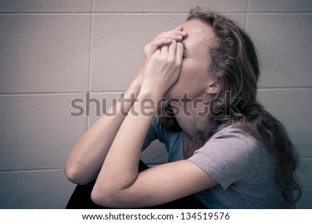 one sad woman sitting on the floor near a wall and holding her head in her hands