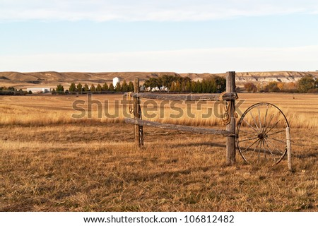 One section of wooden fence with ropes on each end and an old wagon wheel in a rural, agricultural area