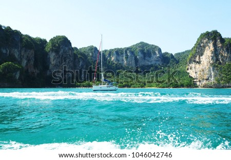 One ship floating in the sea. There are islands in the back at Krabi Thailand.