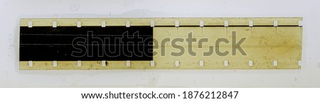 Photo of  one single blank long 16mm filmstrip or snip on white fixed by transparent sticky tape foil. cool photo placeholder with empty frames.