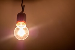 One single old plain bright incandescent lightbulb on in a darkened room, object detail, closeup, from below Bright yellow light source illuminates the room, light in the dark abstract concept, nobody