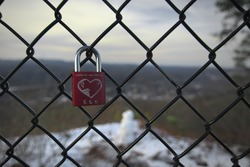 One single padlock with a heart scratched carved into it with initials and the a love quote attached to a fence surrounding Flag Rock at Norton Virginia
