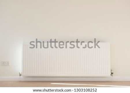 One single radiator single white in lounge neutral background carpet and wall for home heating