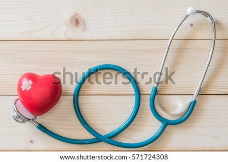 One single red heart love shape with cross bandage and medical doctor physician's stethoscope on white wood background: Hospital healthcare insurance business conceptual idea: World health day concept