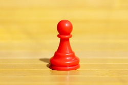 One single red pawn, solo chess piece, distinct game piece standing alone. Independence, freedom, loneliness and isolatoion abstract concept. Lone red pawn in a vast empty space, nobody, closeup