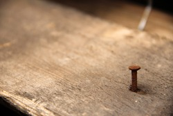 One single rusty nail stuck in an old wooden plank