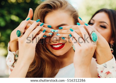 One sister closes her eyes another bright beautiful nail Polish,jewelry, rings