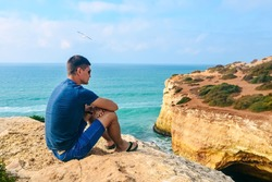 one slender handsome guy with glasses sits on stones on a rock in Portugal. back view of the ocean