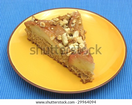 One slice of  a wholemeal apple cake on blue placemat