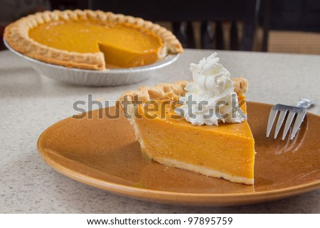 one slice of pumpkin  pie removed from the whole and ready to eat - stock photo