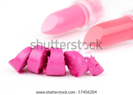 One sliced lipstick and two whole lipsticks in distance, closed-up on white