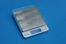 one small gray empty scales with electronic display stands on a blue table