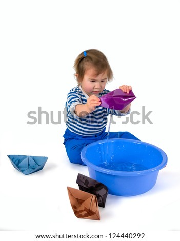 One small little girl wearing frock and blue pants playing with origami paper ships and blue basin.