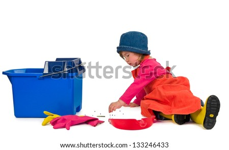 One small little girl wearing orange apron, red t-shirt, blue hat and yellow high boots, cleaning with red scoop and blue bucket. Isolated objects.