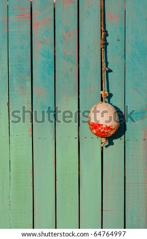 One small white and red fishing buoy hangs on hook in front of brightly painted wooden shack
