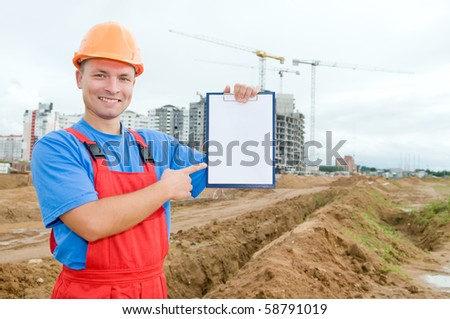 One smiley builder worker pointing the finger to clipboard over construction site