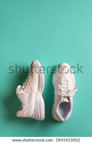 One sneaker stands and the other lies on its side on a green blue background. New white chunky sole shoes for active lifestyle, fitness and sports. Vertical frame with copy space. Top view. Сток-фото ©