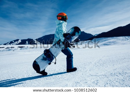 one snowboarder with snowboard walking on winter mountain ski slope #1038512602