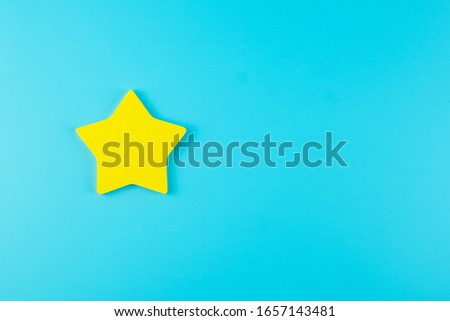 one star yellow paper note on blue background with copy space for text. Customer reviews, feedback, rating, ranking and service concept.