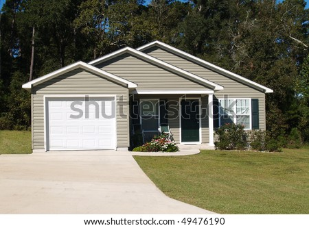 One story residential low income home with gray vinyl siding and front entry garage.