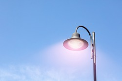 One street lamp with a round shade against a blue sky. City life. Copy space
